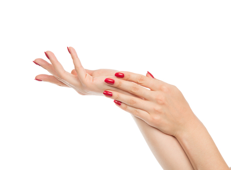 manicured: Woman hands with manicured red nails isolated on a white background. Skin and nail care concept