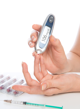 diabetes syringe: Diabetes patient measuring glucose level blood test isolated on a white background