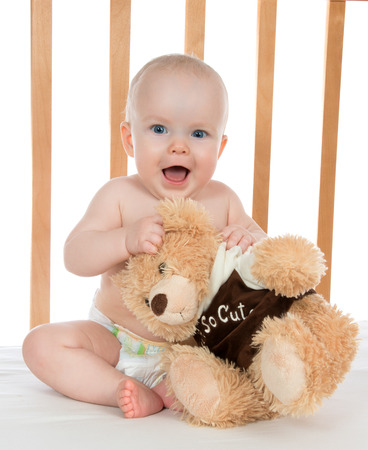 Infant child baby girl shouting in diaper with teddy bear in a bed on white background photo