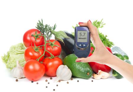 糖尿病概念ブドウ糖メーター手と健康的な有機食品野菜緑アボカド、トマト、きゅうり、サラダ、白い背景の上にコショウ