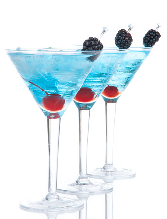 blue hawaiian drink: Closeup blue martini cocktails row composition with alcohol, maraschino cherry, blackberry, vodka, curacao and crushed ice on a white background Stock Photo