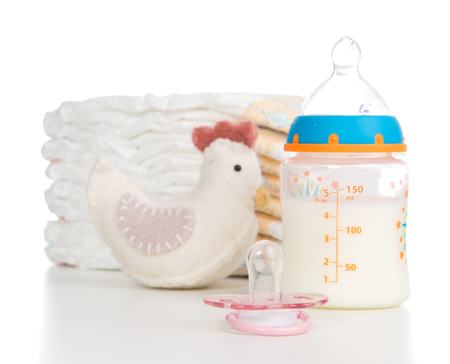 Child stack of diapers, nipple soother, toy and baby feeding bottle with milk on a white background photo