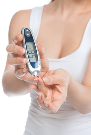 Diabetes patient woman measuring glucose level blood test with glucometer on a white background Stock Photo