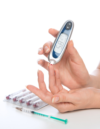 blood glucose: Diabetes hand measuring glucose level blood test with glucometer from finger on a white background
