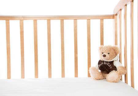 白い背景の上の子供のためのテディベアとベビー ベッド 写真素材