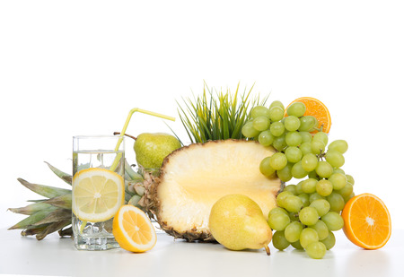 Diet weight loss breakfast concept with organic green grapes, oranges, glass of lemon water juice, pineapple, pears on a white background photo