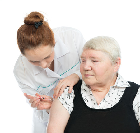 Doctor making senior woman patient an arm subcutaneous insulin medicine syringe injection vaccination shot on a white  photo