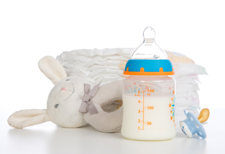 New born child stack of diapers, nipple soother, beanbag bunny toy and baby feeding bottle with milk on a white  Stock Photo