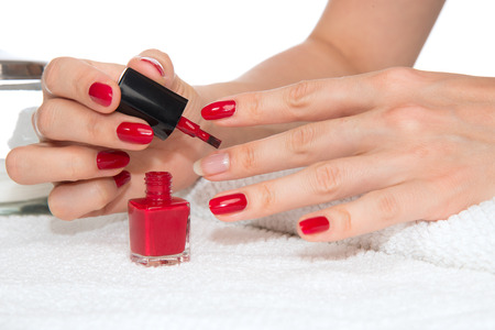 Woman hands doing manicure red nails on a white. Skin and nail care salon concept