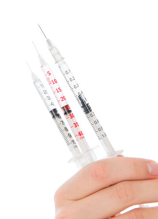 Doctor hand with medical insulin syringes ready for injection isolated on a white  photo