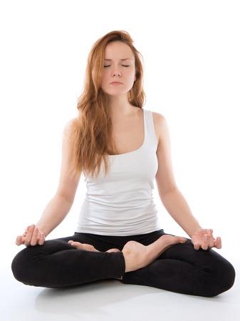 Portret van een jonge vrouw mediteren in yoga pose van lotus op een witte