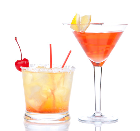 Twee cocktails rode alcohol kosmopolitische cocktail versierd met citrus citroen in martini cocktail glas en gele zomer margarita geïsoleerd op een witte achtergrond Stockfoto