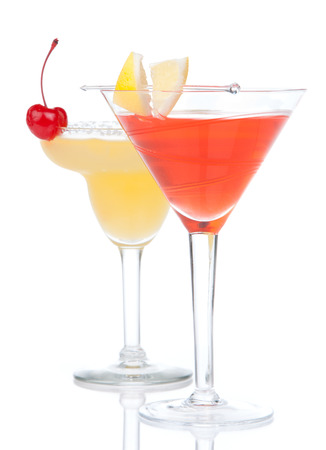 Popular alcoholic cocktails composition. Two cocktail drinks yellow margarita cherry and tropical Martini on a white background
