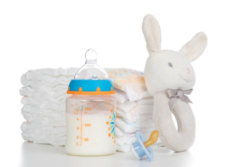 Nieuw geboren kind stapel luiers, tepel fopspeen, zitzak bunny speelgoed en baby zuigfles met melk op een witte achtergrond