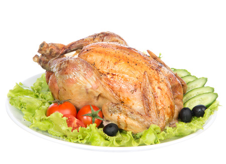 Garnished roasted thanksgiving chicken on a plate decorated with salad, olives, tomatoes, cucumbers isolated on a white  photo