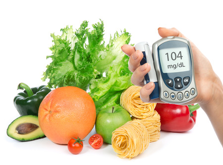 Diabetes concept glucose level blood test meter in hand and healthy organic food fruits and vegetables on a white