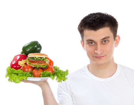 Young man with plate of fresh healthy vegetables salad burger sandwich peppers tomatoes isolated on a white background. Healthy food eating concept photo