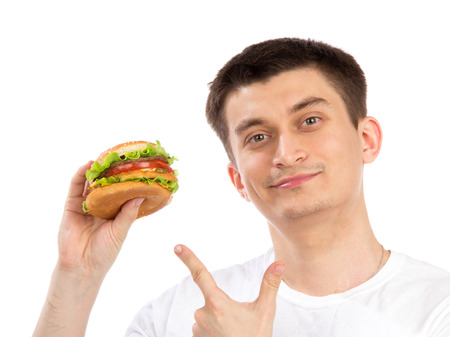 Young man with tasty fast food unhealthy burger sandwich in hand getting ready to eat isolated on a white background photo
