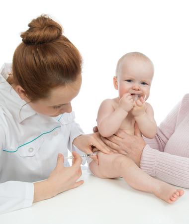 vacunaci�n: Los m�dicos la mano con la jeringuilla vacunar contra la gripe beb� ni�o tiro inyecci�n pierna aislada en un blanco