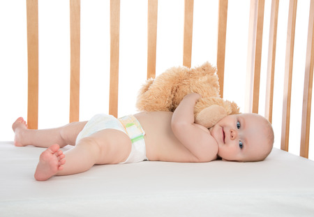 baby diaper: Infant child baby girl toddler lying in bed in diaper hugging teddy bear on white background