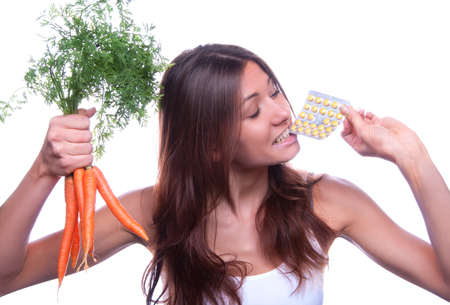 take medicine: Portrait of young beautiful woman hold organic fresh carrots and eat medical tablet pills isolated on a white background