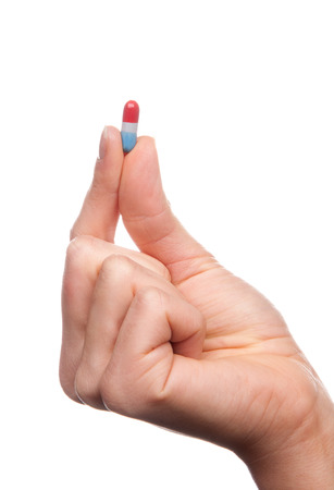 Hand hold medical painkiller pill capsule medicine in red and blue color isolated on a white background photo