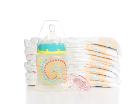 incontinence: New born child stack of diapers, nipple soother baby feeding bottle with water on a white background