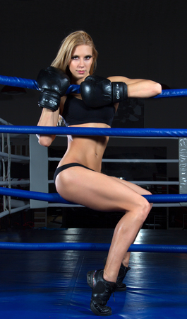Sport Boxing Woman in black box gloves hit punching ball in fitness gym on a black background photo