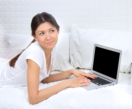 Young successful woman lying on a sofa with laptop paying bills online looking up and thinking photo