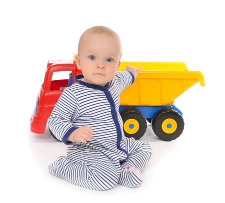 crawl: Cute child baby boy toddler happy sitting with big toy car truck red yellow and blue colors in hand on a white background
