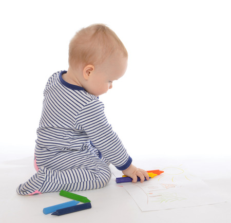 Child baby toddler sitting drawing painting with colour pencils crayons on a white background photo