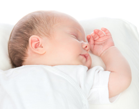 New born infant child baby girl sleeping on a back in white shirt on a white background Stock Photo