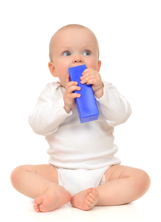 child sitting: Cute child baby girl toddler sitting and eating blue toy brick in hand on a white background Stock Photo
