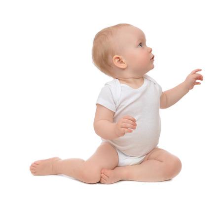 10 ヶ月赤ちゃん幼児、白い背景で隔離されたコーナーで幸せなポインティング指手を座っています。