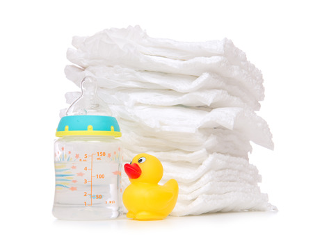 New born child stack of diapers, nipple soother, baby feeding milk bottle with water and yellow duck on a white background photo