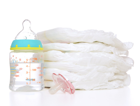 New born child stack of diapers, nipple soother,  baby feeding milk bottle with water on a white background photo
