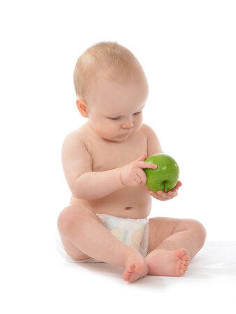 Happy child baby toddler sitting in diaper with green apple isolated on a white background photo