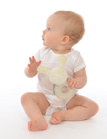 Infant child baby toddler sitting smiling with soft bunny toy looking at te corner on a white background photo