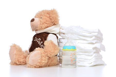 Child stack of diapers and baby feeding bottle with water and soft teddy bear toy on a white background