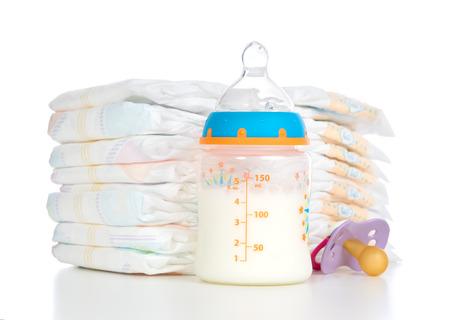 Nouvelle pile de l'enfant né de couches mamelon sucette et biberon de bébé avec du lait sur un fond blanc Banque d'images - 27807133