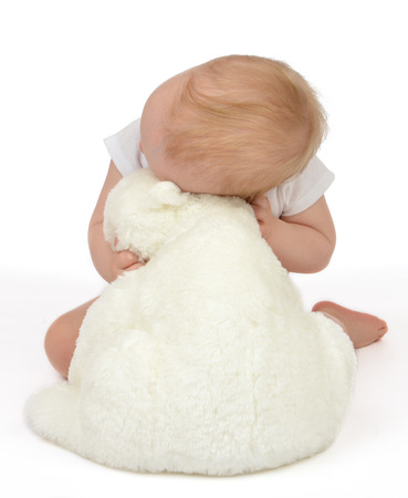 Infant child baby girl hugging soft teddy bear sleeping on a white background photo