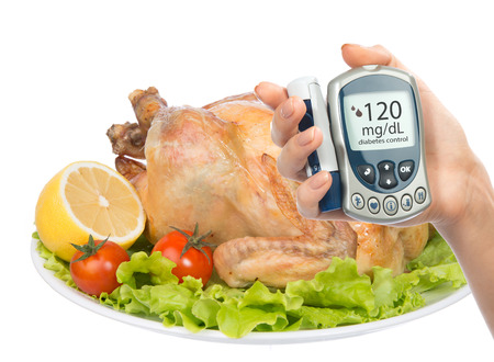 blood sugar: Diabetes concept glucose meter in hand and garnished roasted chicken meal on a plate with salad lemon tomatoes isolated on a white background