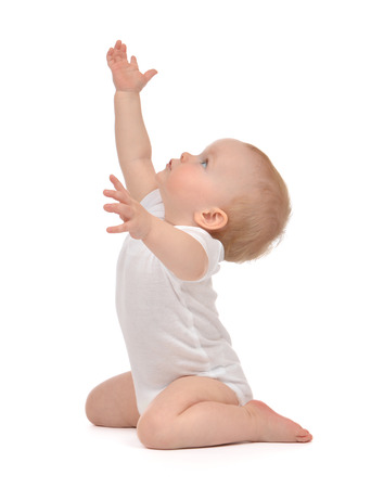 Infant child baby toddler sitting raise hands up isolated on a white background Stock Photo