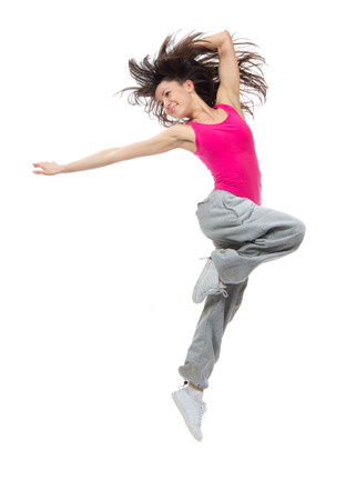 新しいかなりモダンなスリムなヒップホップ スタイル ダンサー 10 代の少女ダンス スタジオの白い背景で隔離のジャンプ