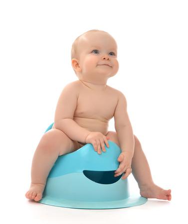 Infant child baby boy toddler sitting on potty toilet stool pot isolated on a white background