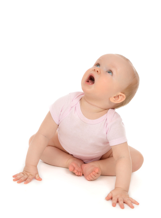 Infant child baby toddler sitting looking up and yelling isolated on a white background Stock Photo