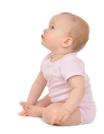 Infant child baby toddler sitting happy looking at the corner on a white background Stock Photo