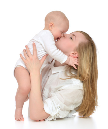 Young mother woman holding kissing and laughing infant child baby kid girl on a white background photo