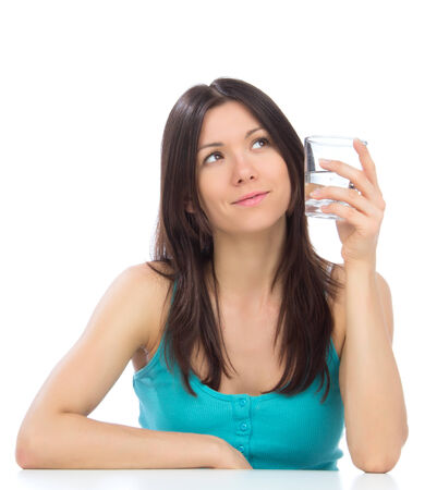 Woman getting ready to drink glass of drinking water. Healthy weight loss concept on a white background