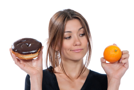 Healthy eating food concept. Woman comparing unhealthy donut and orange fruit, thinking isolated on a white background